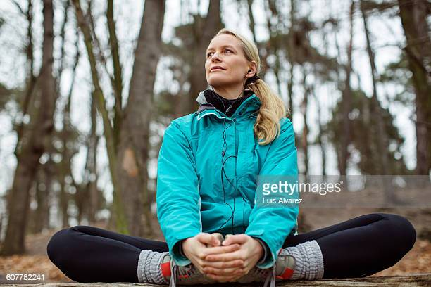 Thoughtful woman exercising in forest