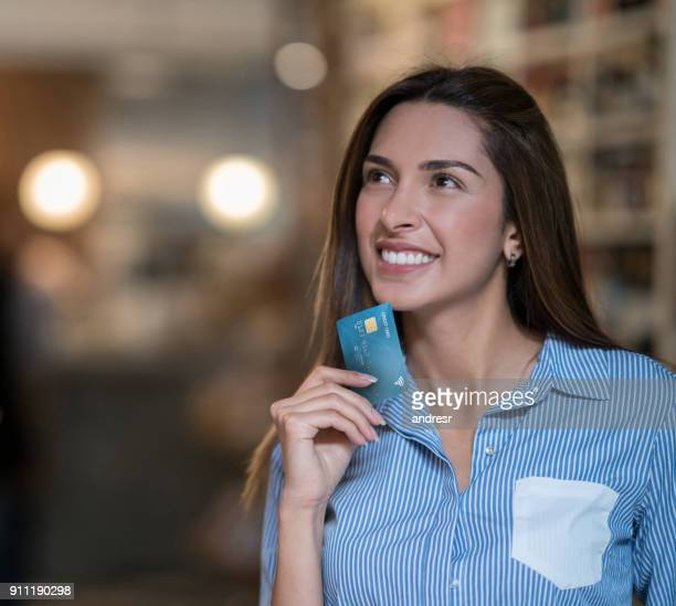 thoughtful woman grocery shopping holding a credit card - thinking of you card stock pictures, royalty-free photos & images