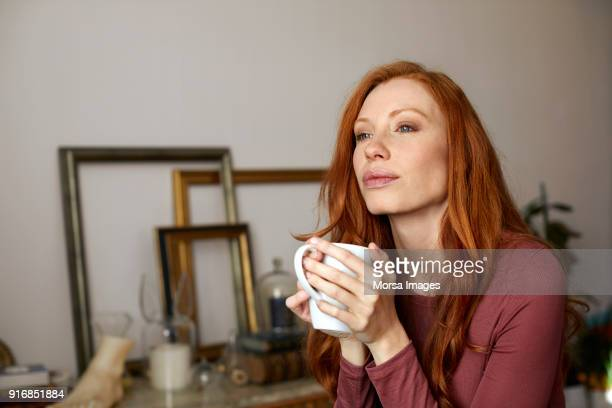 thoughtful woman having coffee from mug at home - hygge stock pictures, royalty-free photos & images