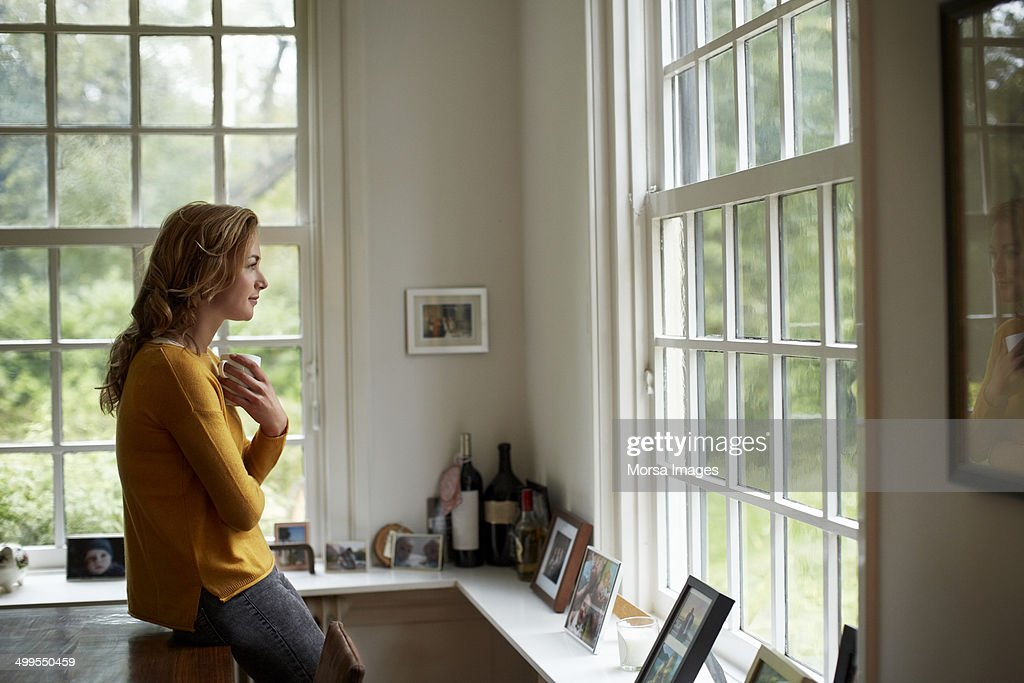 Thoughtful woman having coffee in cottage : Stock Photo