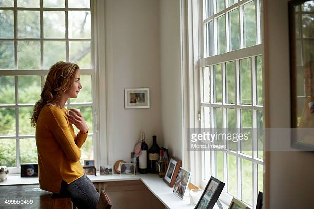 thoughtful woman having coffee in cottage - vrouw stockfoto's en -beelden