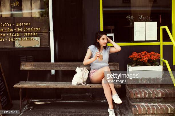 thoughtful woman having coffee while sitting on bench at sidewalk cafe in city - bench stock pictures, royalty-free photos & images