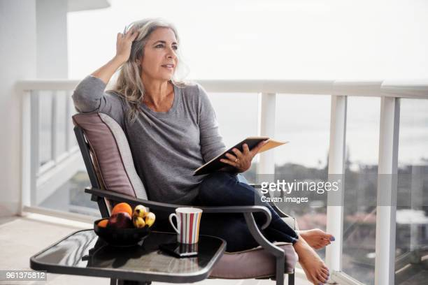 thoughtful woman holding book while sitting on chair on balcony - aventura stock pictures, royalty-free photos & images