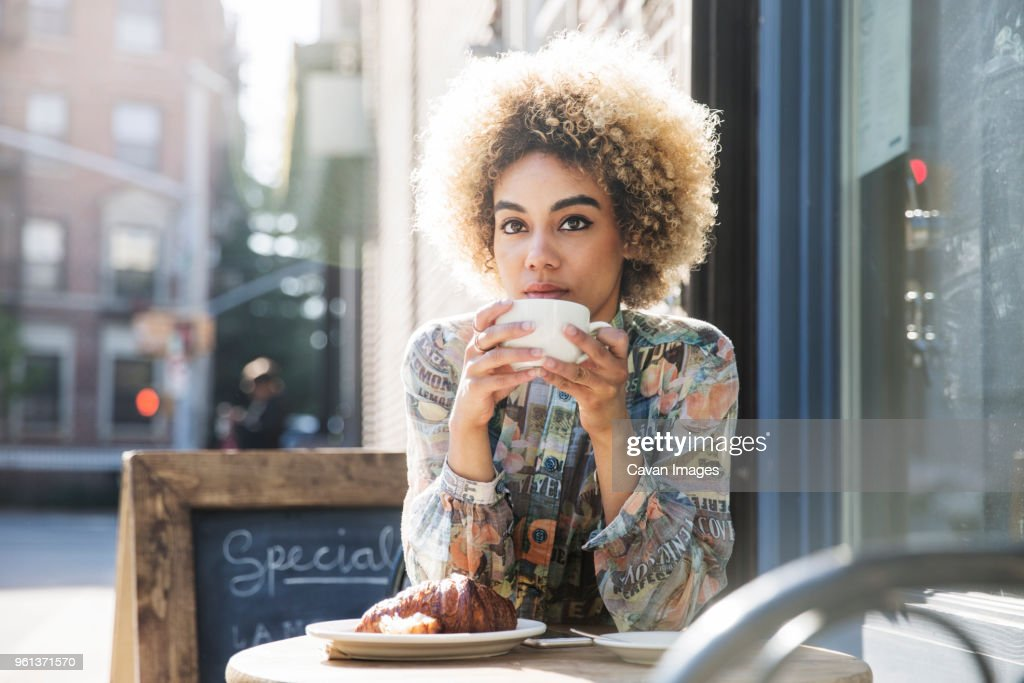 Thoughtful woman holding coffee cup while sitting at sidewalk cafe : Stockfoto