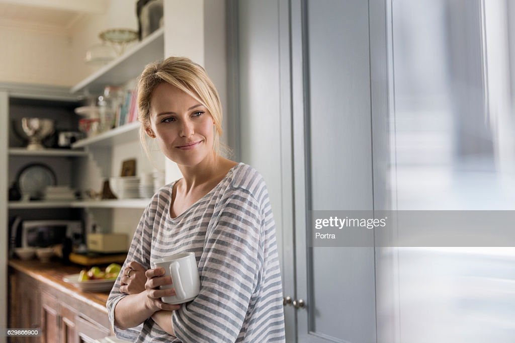 Thoughtful woman holding coffee mug by window : Stock Photo