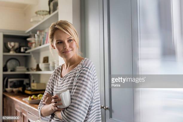 thoughtful woman holding coffee mug by window - pretty blondes stock pictures, royalty-free photos & images