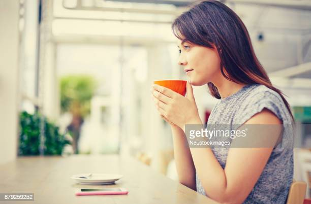Thoughtful woman holding coffee mug while sitting at cafe