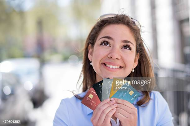 Thoughtful woman holding credit cards