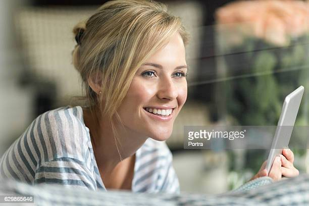 Thoughtful woman holding digital tablet at home