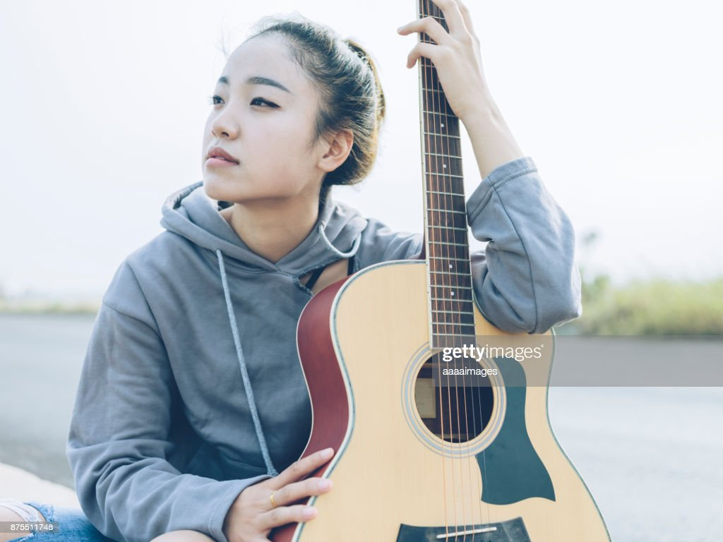 thoughtful woman holding guitar sitting at roadside : Stock Photo