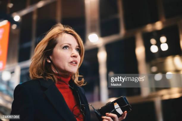Thoughtful woman holding mobile phone at illuminated railroad station