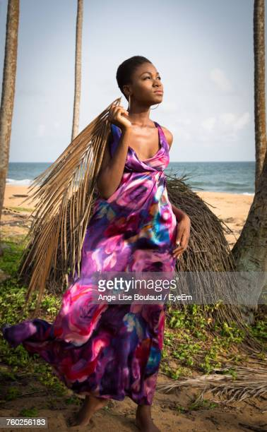 thoughtful woman holding palm leaves while standing on shore at beach - femme ivoirienne photos et images de collection