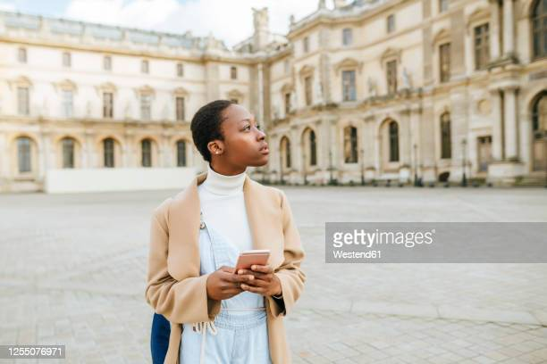 thoughtful woman holding smart phone at town square with building in background at paris, france - junge frau allein stock-fotos und bilder