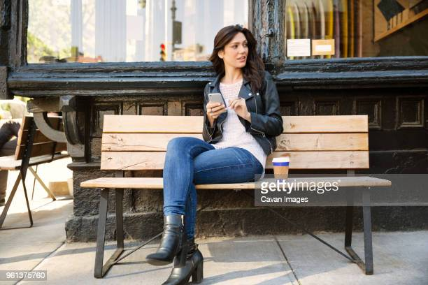 thoughtful woman holding smart phone while sitting on bench at sidewalk cafe - sitting stock pictures, royalty-free photos & images