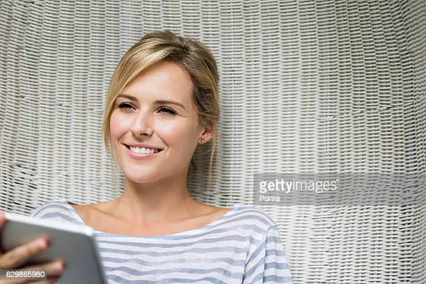Thoughtful woman holding tablet PC on wicker chair