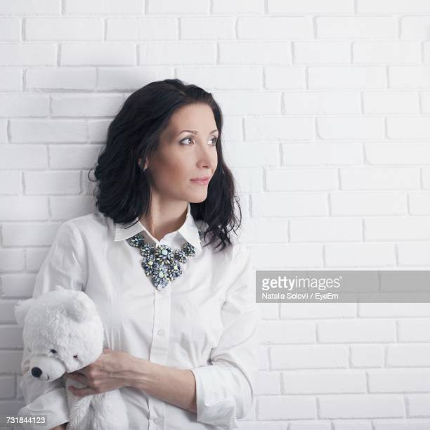 Thoughtful Woman Holding Teddy Bear While Standing By White Brick Wall