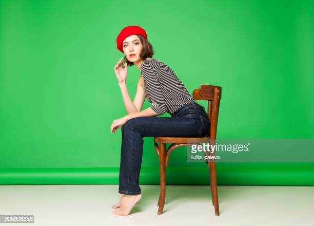 thoughtful woman in beret on chair - ベレー帽 ストックフォトと画像