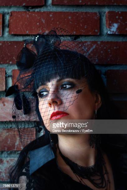 Thoughtful Woman In Widow Hat Looking Away Against Brick Wall