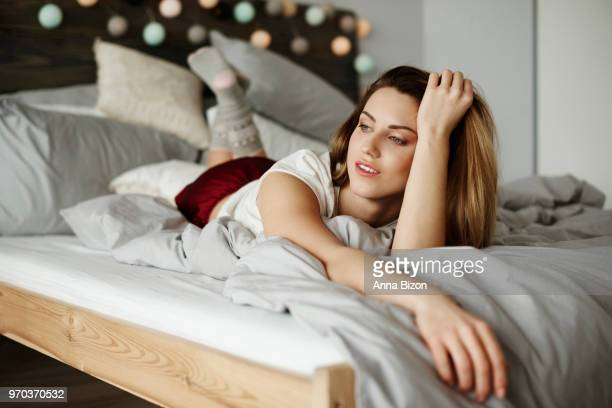 thoughtful woman laying on stomach in bedroom. debica, poland - lazy poland stock photos and pictures