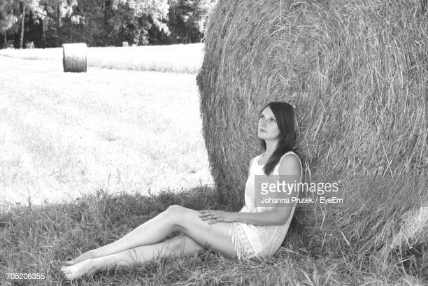 thoughtful woman leaning on hay bale while sitting at farm field - johanna roll stock-fotos und bilder