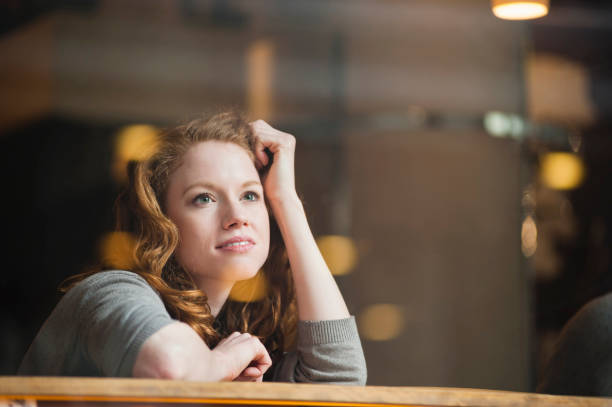 thoughtful woman leaning on table seen through glass window in coffee shop - woman dream stock pictures, royalty-free photos & images