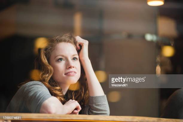 thoughtful woman leaning on table seen through glass window in coffee shop - rêvasser photos et images de collection