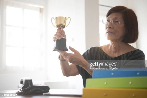 Thoughtful Woman Looking Away While Holding Trophy At Office