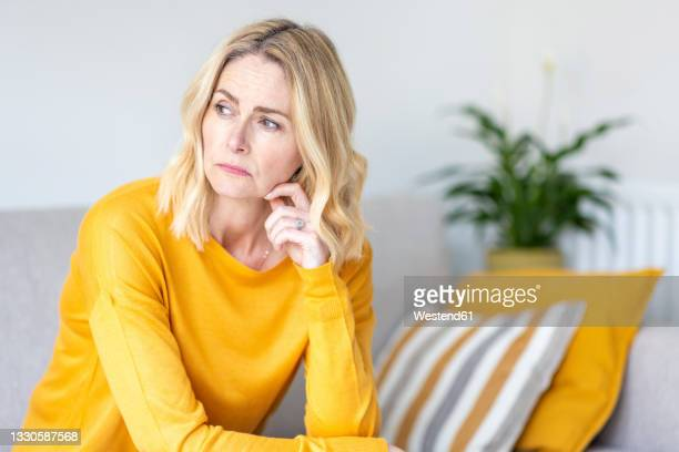 thoughtful woman looking away while sitting at home - depression sadness stock pictures, royalty-free photos & images