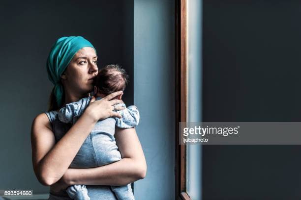 Thoughtful woman looking out the window while holding her son