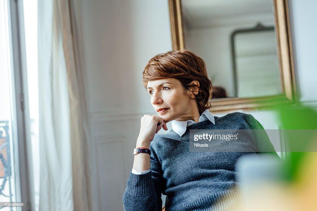Durchdachte Frau schaut dem Fenster : Stock-Foto