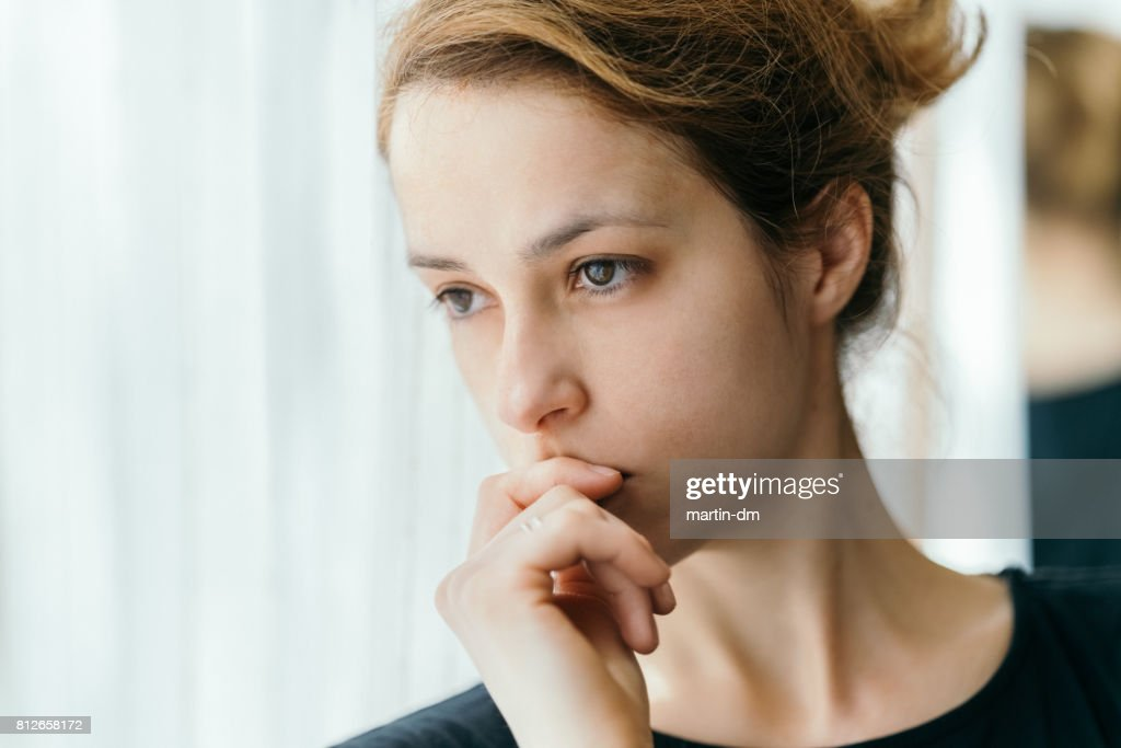 Thoughtful woman looking through the window : Stock Photo