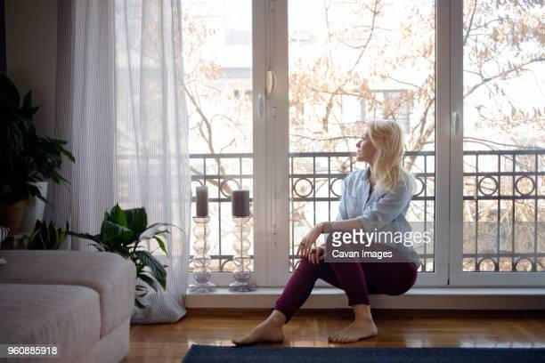 thoughtful woman looking through window at home - donne di età media foto e immagini stock