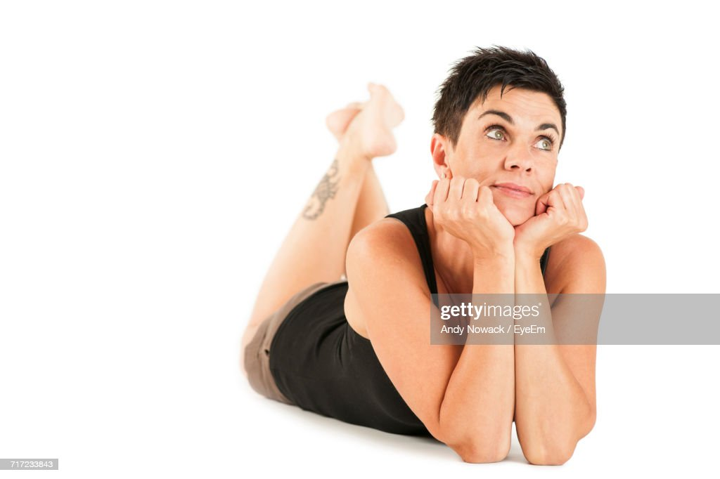 Thoughtful Woman Lying Against White Background : Stock Photo