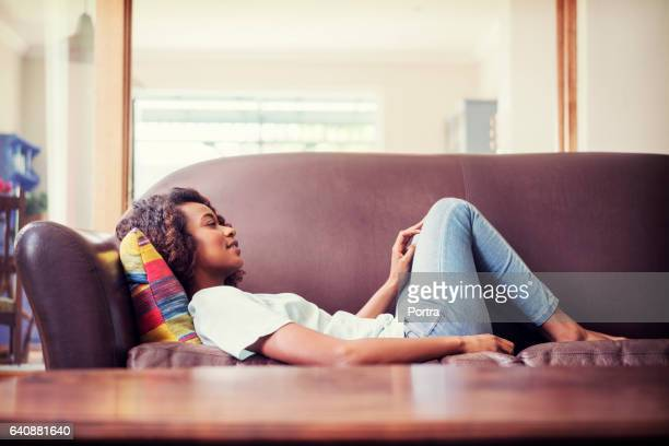 Thoughtful woman lying on sofa at home