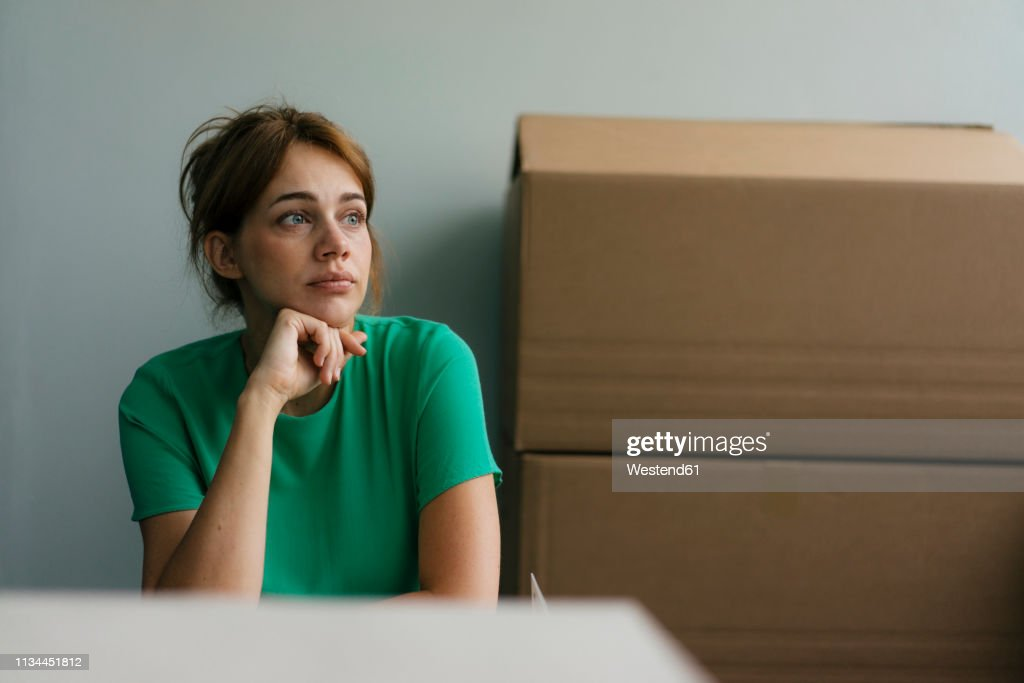 Thoughtful woman next to cardboard boxes in office : Stockfoto