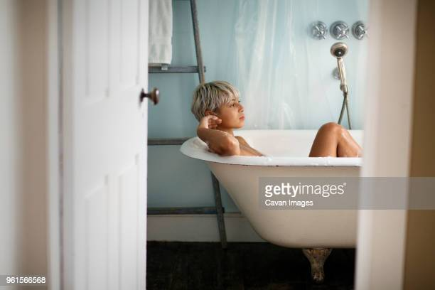 thoughtful woman relaxing in bathtub at home - jeune femme sous la douche photos et images de collection