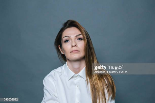 thoughtful woman sitting against gray background - uncomfortable stock pictures, royalty-free photos & images