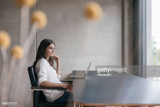 thoughtful woman sitting at table with laptop - contemplation office stock-fotos und bilder