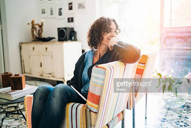 thoughtful woman sitting on chair at home - belle femme africaine photos et images de collection