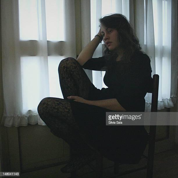 thoughtful woman sitting on chair - endast en ung kvinna bildbanksfoton och bilder