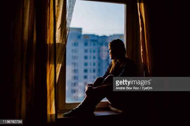 thoughtful woman sitting on window at home - despair stock pictures, royalty-free photos & images