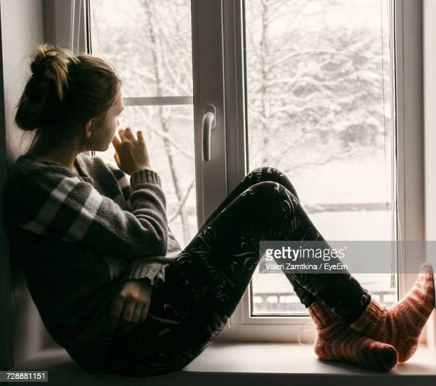 Thoughtful Woman Sitting On Window Sill During Sunny Day