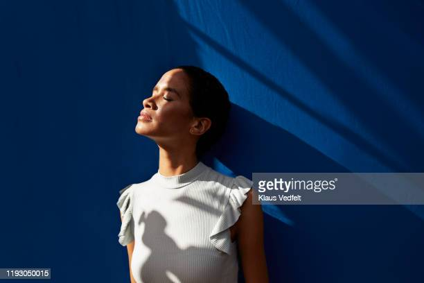 thoughtful woman standing against blue wall - beschaulichkeit stock-fotos und bilder