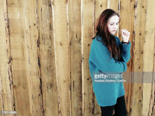 thoughtful woman standing against wooden wall - anastasi foto e immagini stock