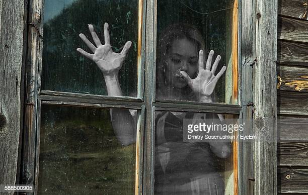 Thoughtful Woman Standing Behind Window Of Old House