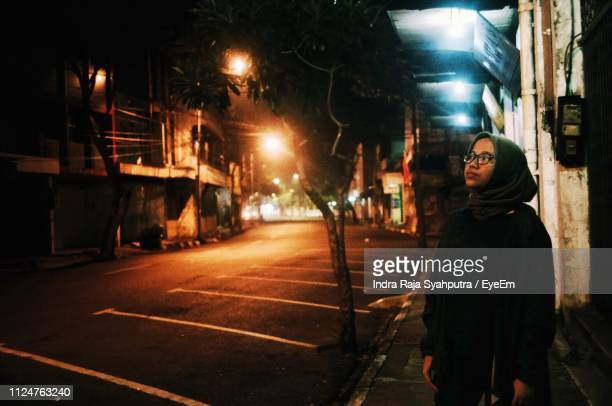 thoughtful woman standing on sidewalk in illuminated city at night - surabaya stock pictures, royalty-free photos & images