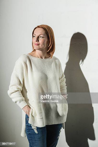 Thoughtful woman standing with hands in pockets against white background