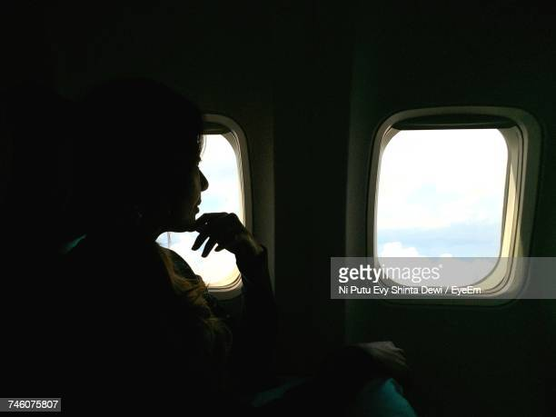 Thoughtful Woman Traveling In Airplane