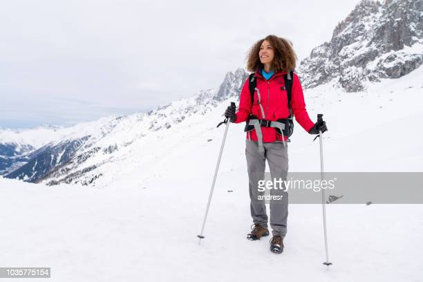 thoughtful woman trekking in the snow mountains - female skier stock pictures, royalty-free photos & images