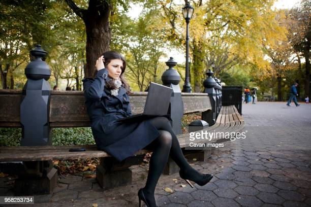 Thoughtful woman using laptop while sitting on bench in Central Park